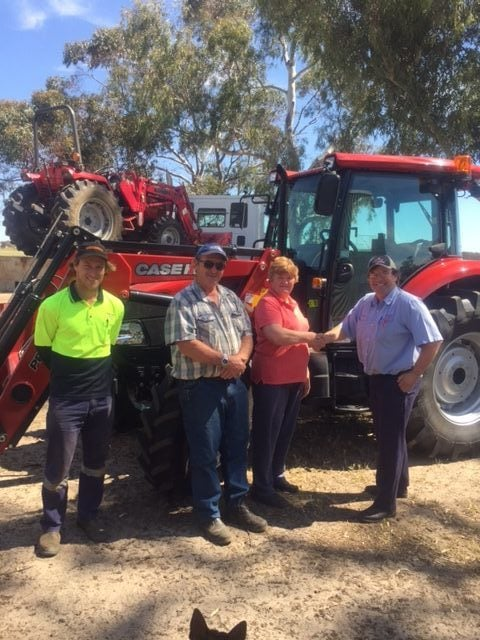 Boekeman Machinery employees congratulating Heather Dixon on her purchase of the new CASEIH Farmall JX90 Cab 4wd Tractor