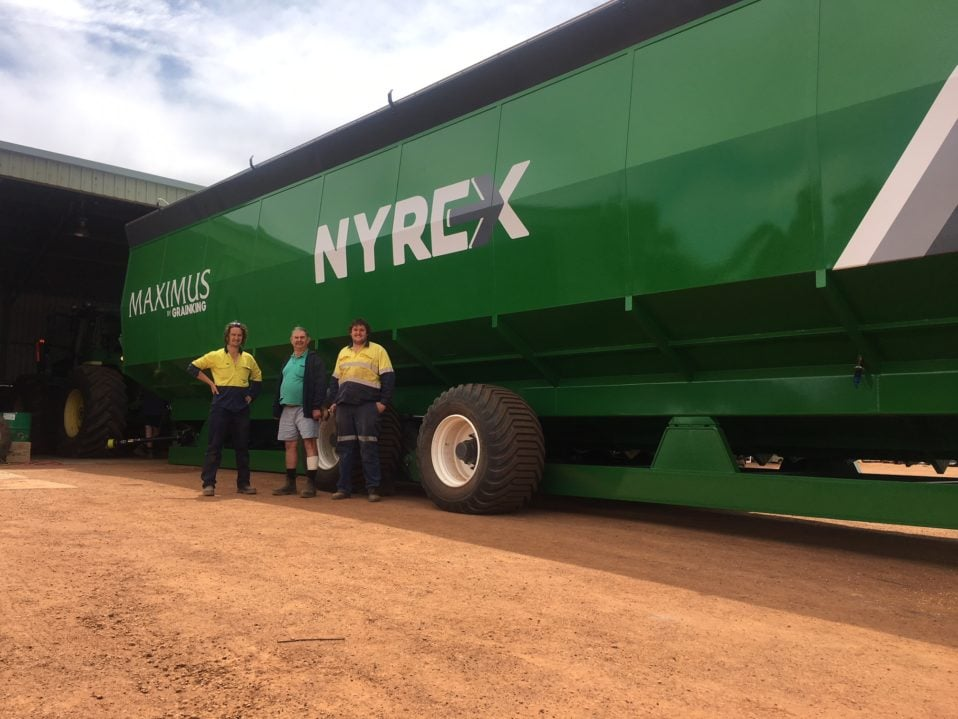 Boekeman Machinery employees congratulating Hyde Park on his purchase of the new Nyrex 40000 32T Tandem Axle Chaser Bin