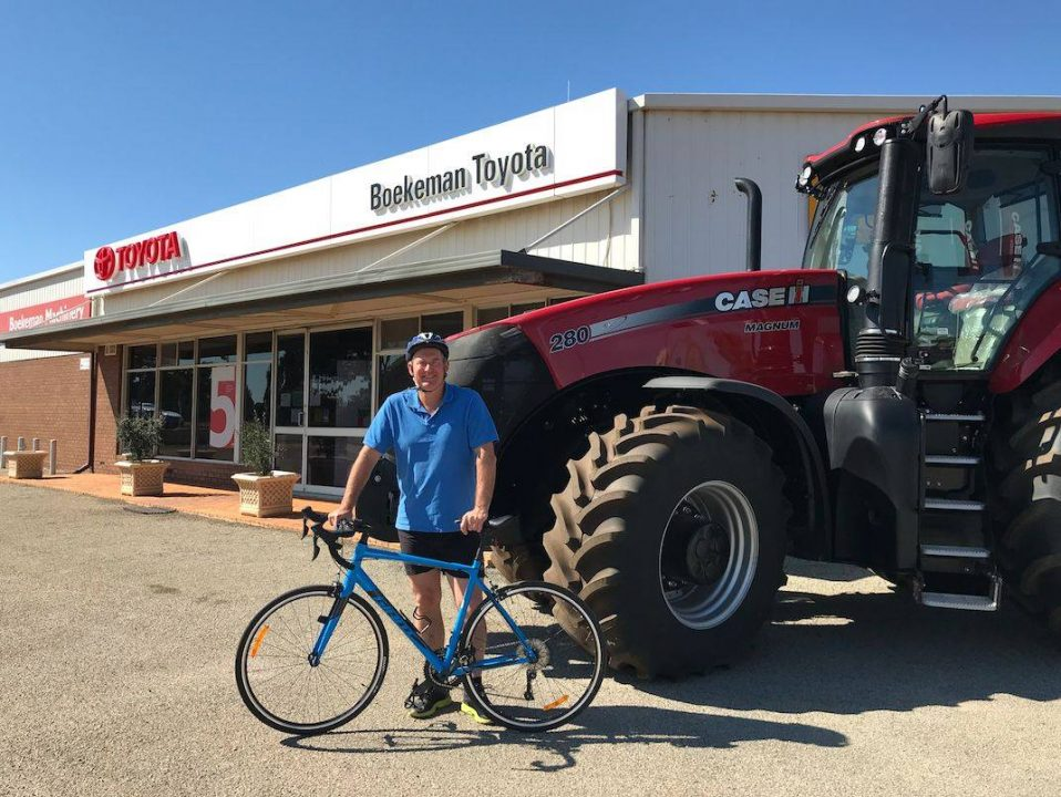 Stuart Boekeman with his road bike and a Case IH Magnum 280 on the background