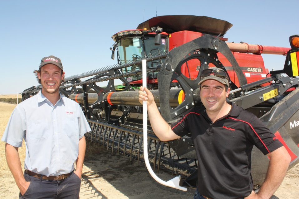 Ben Boekeman and Chris CouchiMacDon with a D145 draper front mounted on a Case IH 8240 Combine Harvester on the background