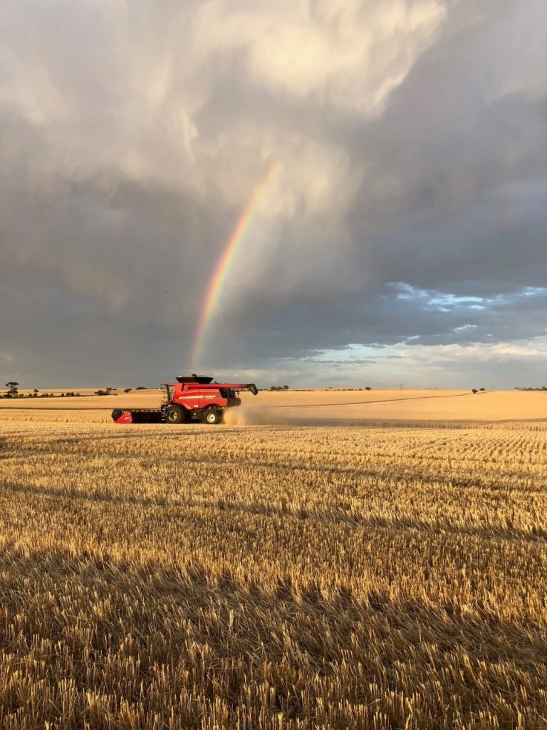 """A photo called """"Pot of Gold in the Paddock"""" with the rainbow on top of a CASEIH 6130 Axial-Flow harvester in the field"""