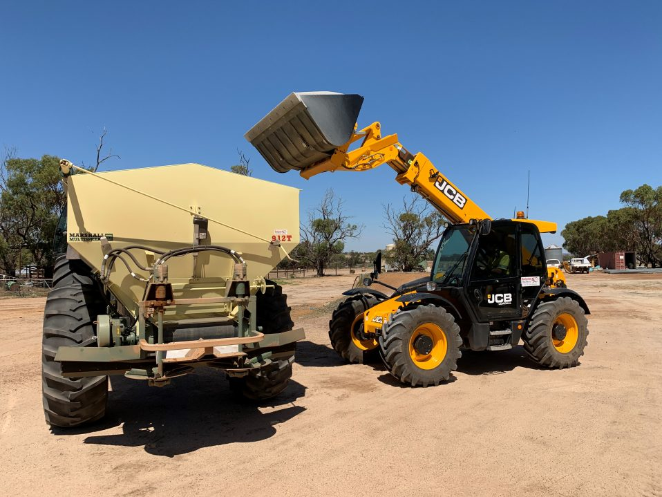A JCB 541-70 T4i transferring sand on its loader to a Marshall 912T Multispreader