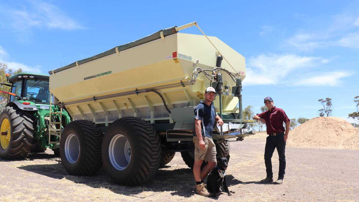 Mr. Reynold and his son, along with their dog, are leaning on a spreader